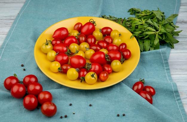 Vista lateral de tomates amarelos e vermelhos no prato e folhas de hortelã verde no pano azul