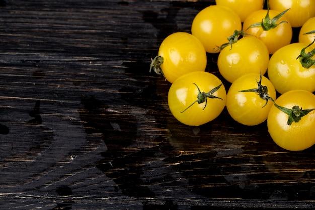 Vista lateral de tomates amarelos na madeira com espaço de cópia