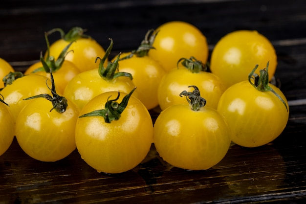 Vista lateral de tomates amarelos na superfície de madeira