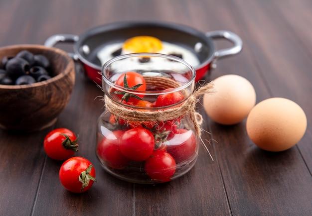 Vista lateral de tomates em uma jarra de vidro com uma tigela de ovos de azeitona preta e uma frigideira de ovo frito na madeira