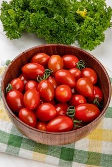 Vista lateral de tomates em uma tigela no pano com coentro chinês na mesa de madeira