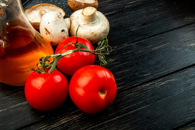 Vista lateral de tomates frescos de cogumelos brancos e uma garrafa de azeite na mesa de madeira escura com espaço de cópia