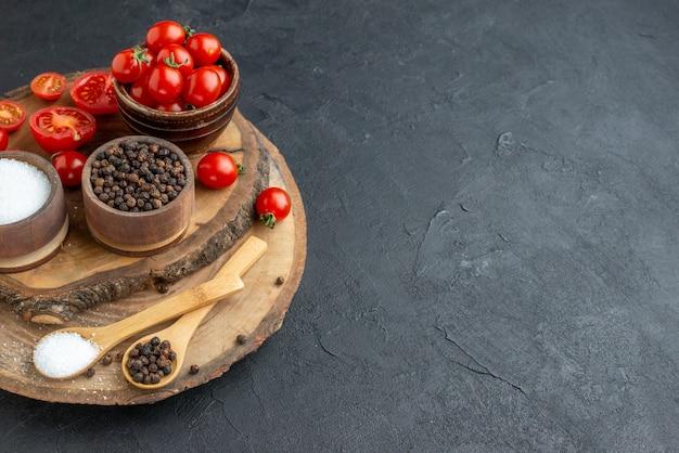 Vista lateral de tomates frescos e especiarias na placa de madeira na superfície preta
