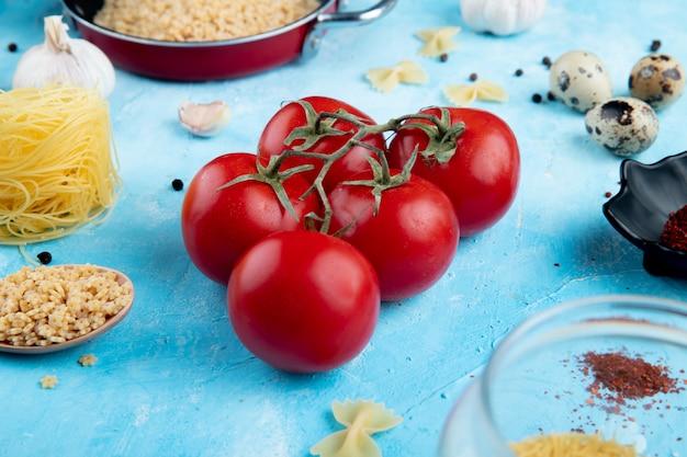 Vista lateral de tomates frescos e estrelas cruas em forma de macarrão no azul