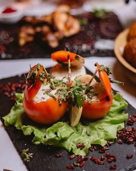 Vista lateral de tomates recheados com molho de creme de verduras e molho de pesto e bérberis secas em um prato