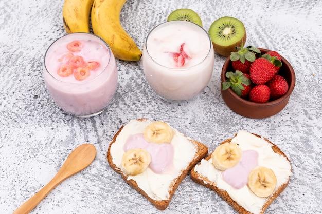 Vista lateral de torradas com iogurte e frutas na superfície branca horizontal