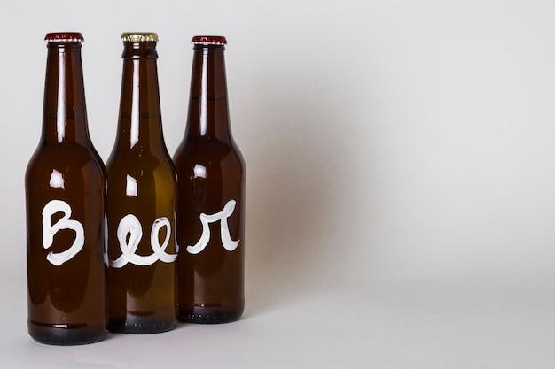 Vista lateral de três garrafas de cerveja na mesa