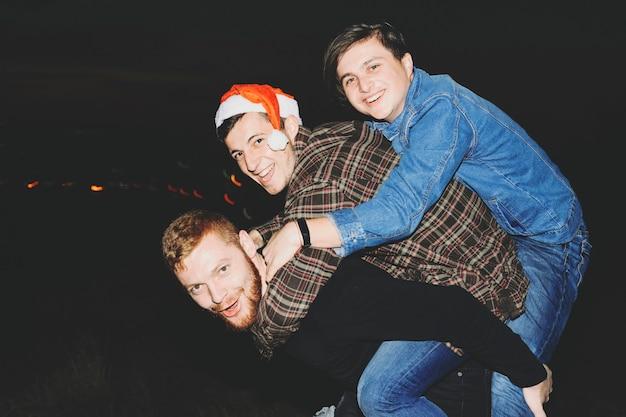 Vista lateral de três jovens em roupas casuais sorrindo e olhando para a câmera enquanto se divertem durante a celebração do natal na noite escura no campo