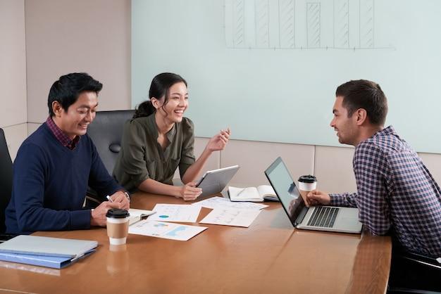 Vista lateral de três pessoas na reunião de negócios