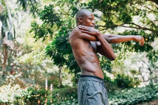 Vista lateral, de, um, africano, homem jovem, fazendo, esticando exercício, parque