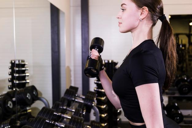 Vista lateral, de, um, ajuste, mulher jovem, fazendo, exercício, com, dumbbell