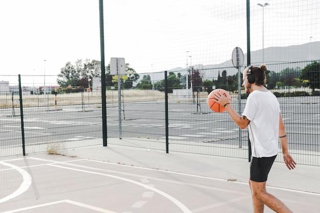Vista lateral, de, um, andar homem, com, basquetebol, em, corte