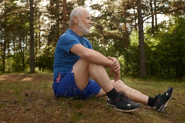 Vista lateral de um aposentado elegante com barba, contemplando a bela paisagem sentado na borda da floresta, relaxando após o treino cardiovascular matinal, abraçando os joelhos com os dois braços, tendo um olhar calmo e tranquilo
