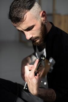 Vista lateral de um artista masculino tocando guitarra elétrica