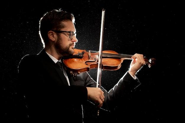 Vista lateral de um artista masculino tocando violino