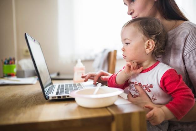 Vista lateral, de, um, assento mulher, com, dela, criança, usando computador portátil, sobre, escrivaninha madeira