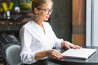 Vista lateral, de, um, assento mulher, em, restaurante, com, laptop