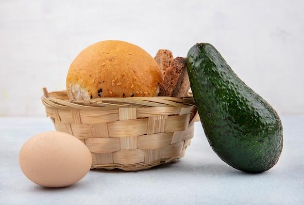 Vista lateral de um balde de pães com abacate e ovo na superfície branca
