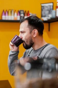 Vista lateral de um barista bebendo café