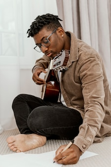Vista lateral de um belo músico escrevendo letras e segurando uma guitarra