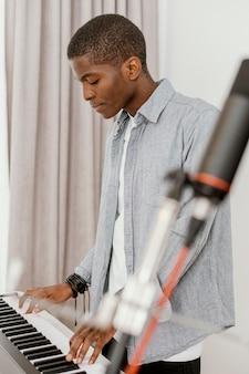 Vista lateral de um belo músico masculino em casa tocando teclado elétrico