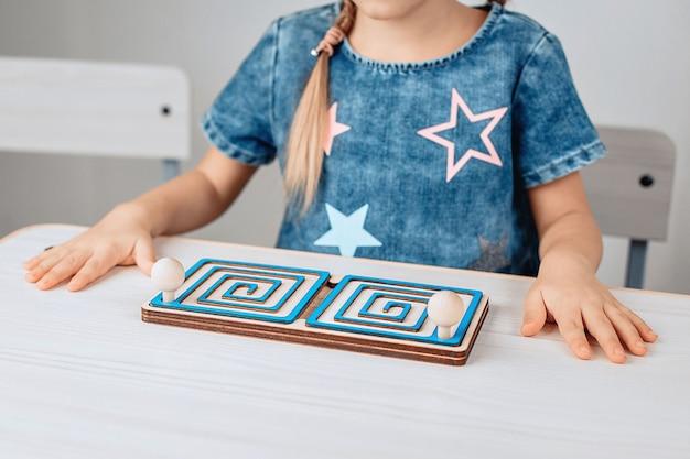 Vista lateral de um belo quebra-cabeça brilhante destinado a desenvolver o pensamento das crianças. garota ao fundo. conceito de desenvolvimento intelectual. foto com ruído