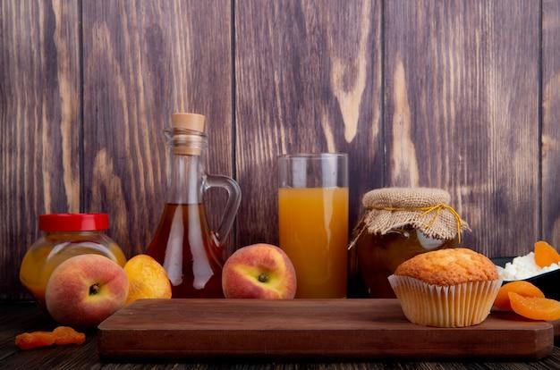 Vista lateral de um bolinho na placa de madeira e pêssegos maduros frescos com um copo de suco de pêssego e geléia de pêssego em uma jarra de vidro no fundo rústico