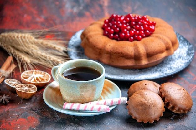 Vista lateral de um bolo com frutas, um bolo apetitoso cupcakes uma xícara de chá doces de anis estrelado