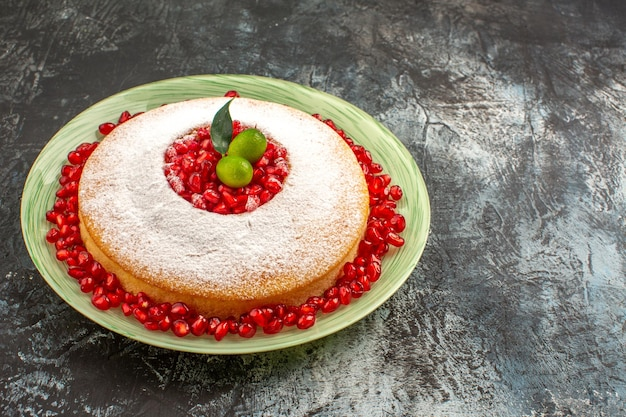 Vista lateral de um bolo com romã um bolo com frutas cítricas e sementes de romã