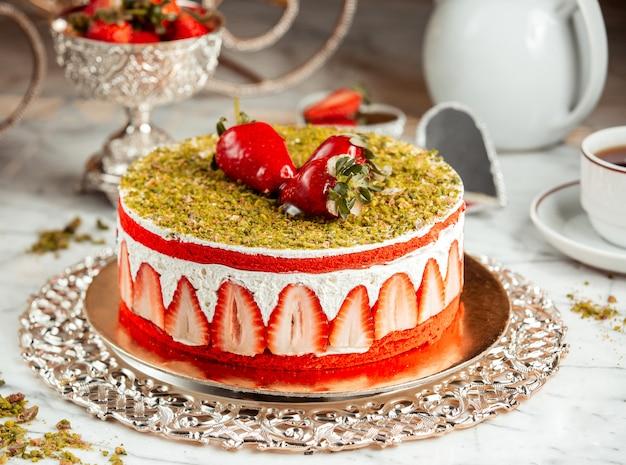 Vista lateral de um bolo de morango com migalhas de pistache em cima da mesa