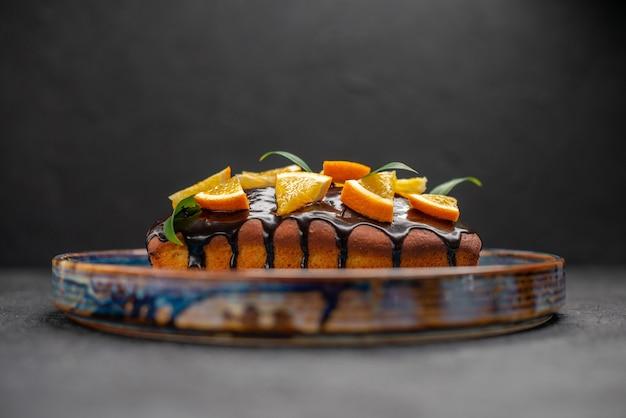 Vista lateral de um bolo macio decorado com laranja e chocolate na mesa escura