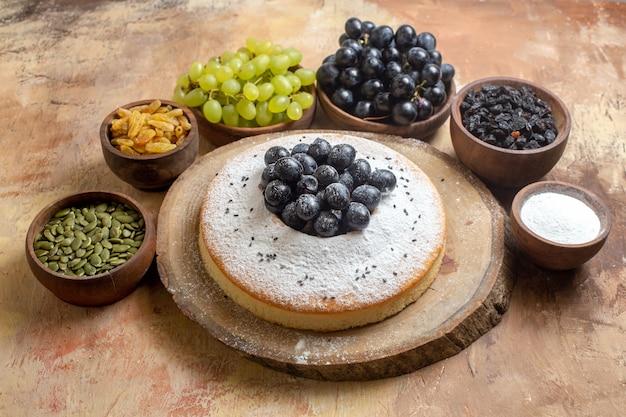 Vista lateral de um bolo um bolo apetitoso com açúcar de confeiteiro no tabuleiro uvas sementes de abóbora passas