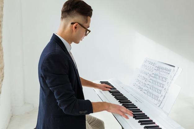 Vista lateral, de, um, bonito, homem jovem, piano jogando