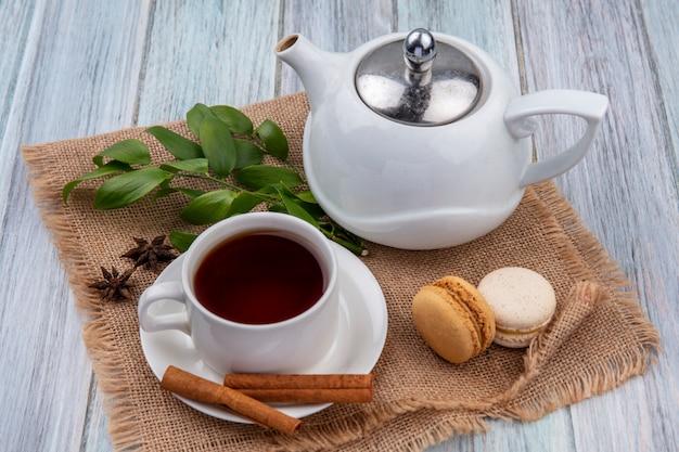Vista lateral de um bule de chá com uma xícara de chá de canela e macarons em um guardanapo bege sobre uma superfície cinza
