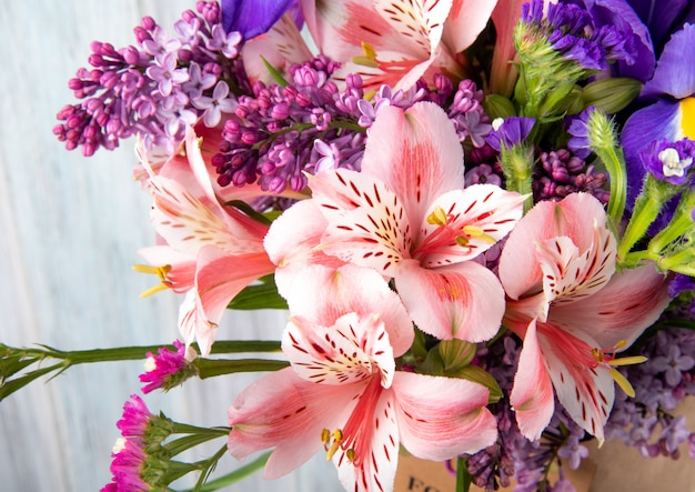 Vista lateral de um buquê de flores cor de rosa e roxo alstroemeria lilás íris e statice em papel ofício em fundo branco de madeira