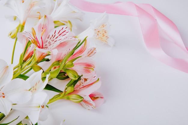 Vista lateral de um buquê de flores de alstroemeria cor de rosa e branco com fita rosa em fundo branco, com espaço de cópia