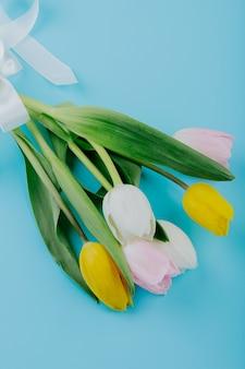 Vista lateral de um buquê de flores de tulipa branco amarelo e rosa cor isoladas em fundo azul