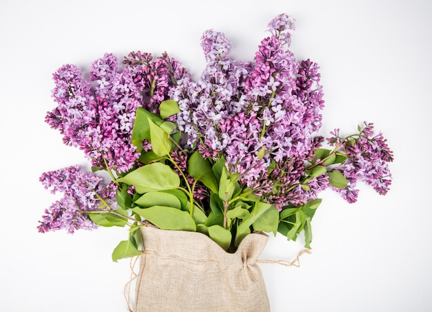 Vista lateral de um buquê de flores lilás em um saco em fundo branco