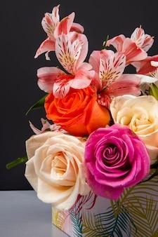 Vista lateral de um buquê de rosas coloridas e flores de alstroemeria cor rosa em uma caixa de presente na mesa preta