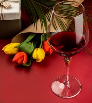 Vista lateral de um buquê de tulipas de cores vermelho e amarelo em papel ofício e um copo de vinho na mesa vermelha