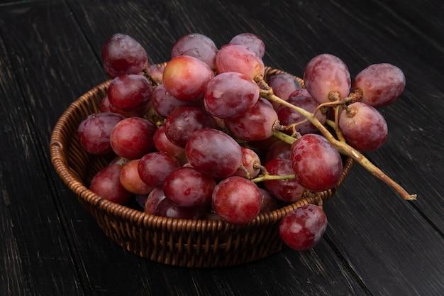 Vista lateral de um cacho de uvas doces frescas em uma cesta de vime na mesa de madeira escura