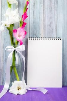 Vista lateral de um caderno de desenho com flores de gladíolo cor branco e rosa em uma garrafa de vidro no fundo cinza de madeira