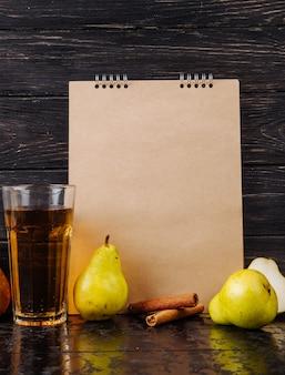 Vista lateral de um caderno de desenho e peras maduras frescas com um copo de suco de pêra em fundo de madeira