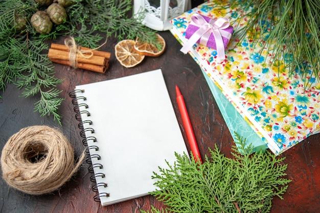 Vista lateral de um caderno fechado com uma caneta de limão, uma bola de ramos de pinheiro e livros em fundo escuro