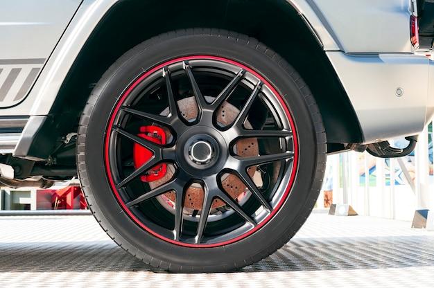 Vista lateral de um carro moderno com pneu de borracha no aro da roda