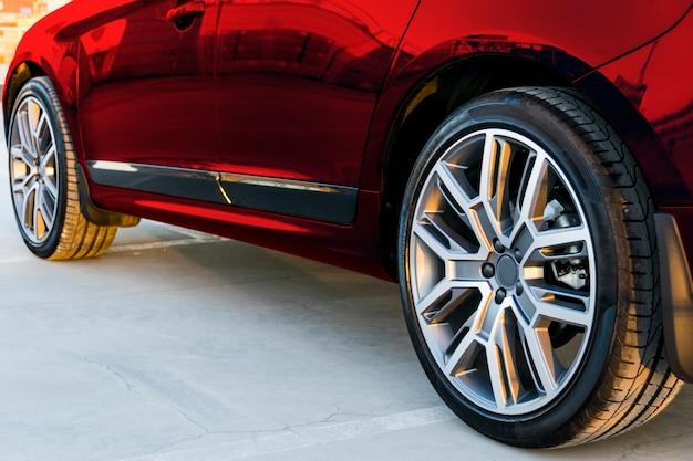 Vista lateral de um carro. pneu e roda de liga leve de um carro vermelho moderno no chão. detalhes do exterior do carro