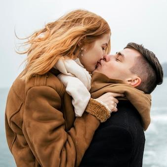Vista lateral de um casal à beira do lago durante o beijo de inverno Foto gratuita
