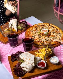 Vista lateral de um casal comendo pizza e doner envolto em lavash servido com batatas fritas e molhos à mesa na mesa