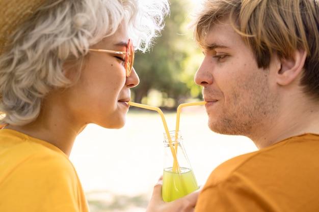 Vista lateral de um casal compartilhando uma garrafa de suco no parque
