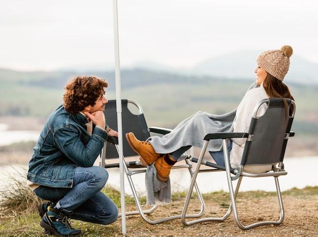 Vista lateral de um casal curtindo a natureza durante uma viagem juntos